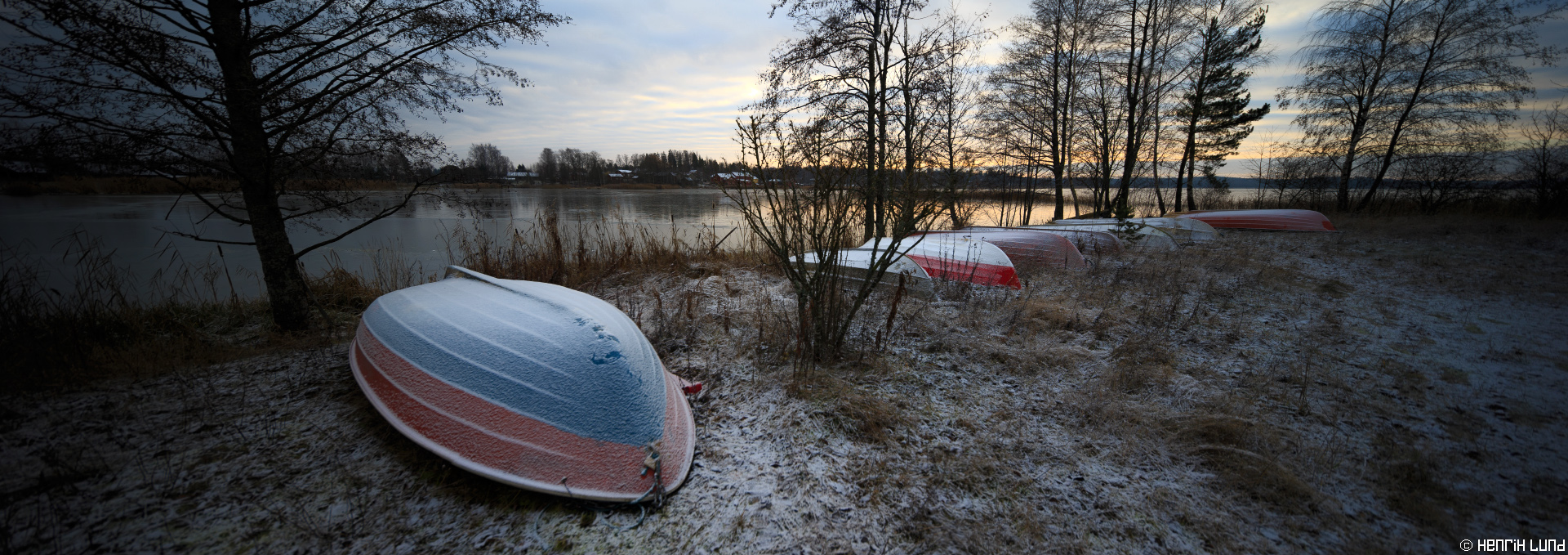 Panoramic view over the first ice cover autumn 2014 - boats are on the shore waiting for the next summer season. Norrby, Lappträsk, Finland. December 2014.