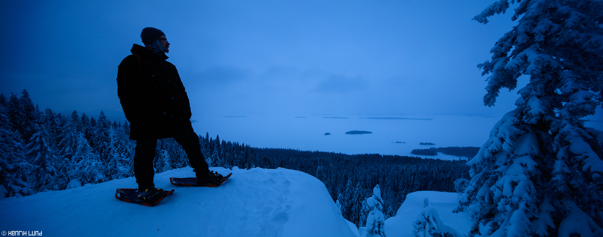 Panoramic view over Pielinen from Koli - Basse on snowshoes posing, Lieksa, Finland. February 2016.