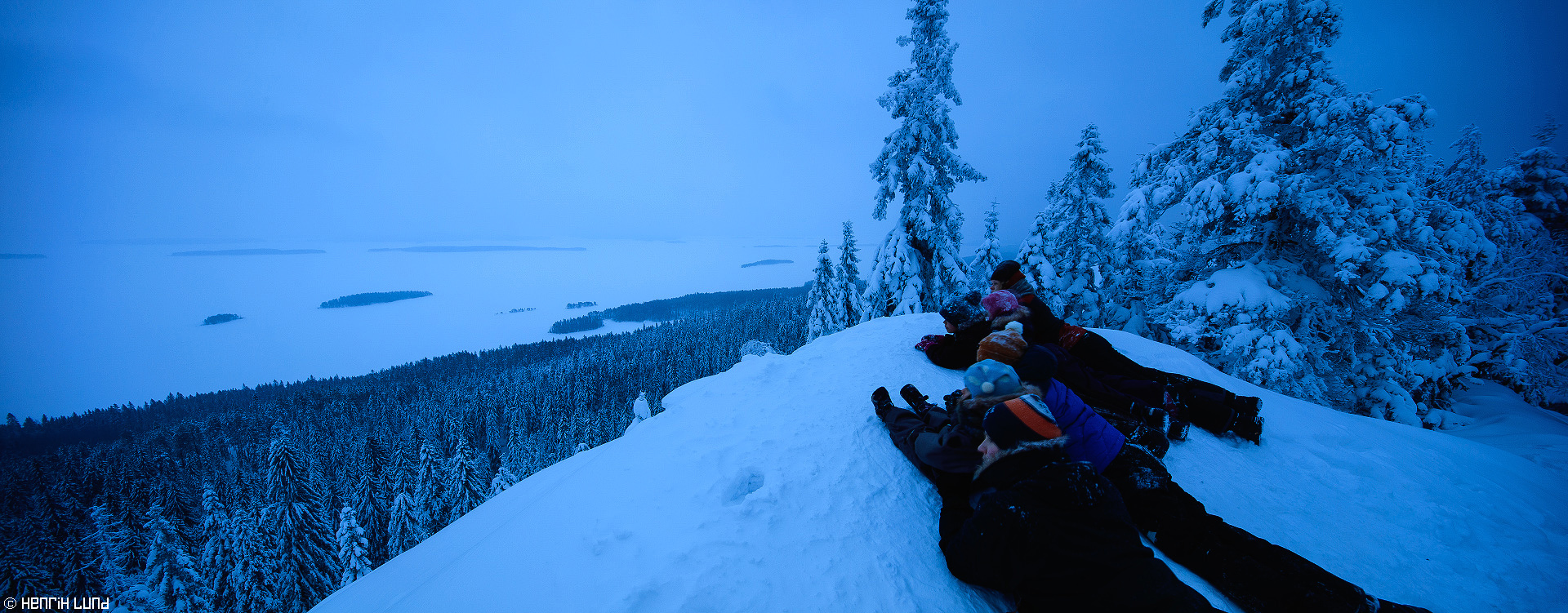 Panoramic view over Pielinen from Koli - children watching over the panoramic scene at blue hour, Lieksa, Finland. February 2016.